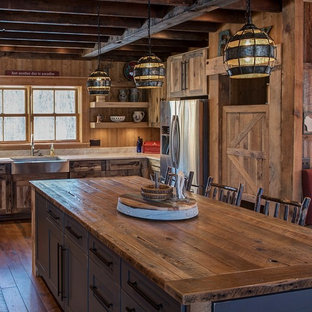 Rustic eat-in kitchen remodeling - Inspiration for a rustic u-shaped eat-in kitchen remodel in Minneapolis with a farmhouse sink, flat-panel cabinets, distressed cabinets, quartzite countertops, stainless steel appliances, an island and wood backsplash