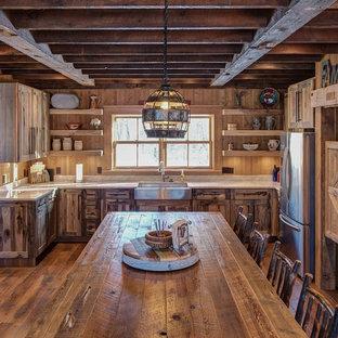 Foto på ett rustikt kök, med en rustik diskho, stänkskydd i trä, mörkt trägolv, släta luckor, skåp i slitet trä, bänkskiva i kvartsit och en köksö