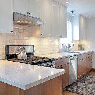 他の地域の小さいカントリー風おしゃれなキッチン (アンダーカウンターシンク、シェーカースタイル扉のキャビネット、白いキャビネット、クオーツストーンカウンター、白いキッチンパネル、セラミックタイルのキッチンパネル、シルバーの調理設備、無垢フローリング、茶色い床、白いキッチンカウンター) の写真