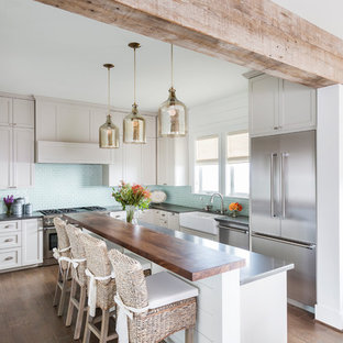 Photo of a beach style u-shaped kitchen/diner in Houston with a double-bowl sink, raised-panel cabinets, white cabinets, zinc worktops, blue splashback, ceramic splashback, stainless steel appliances, an island and dark hardwood flooring.
