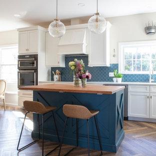 На фото: кухня в стиле современная классика с врезной раковиной, фасадами в стиле шейкер, синими фасадами, деревянной столешницей, синим фартуком, фартуком из керамической плитки, черной техникой, полом из винила, островом и коричневой столешницей с