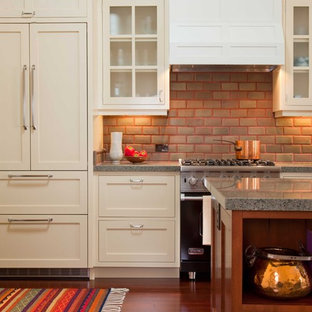 Large traditional enclosed kitchen designs - Enclosed kitchen - large traditional single-wall dark wood floor and brown floor enclosed kitchen idea in San Diego with glass-front cabinets, granite countertops, beige cabinets, red backsplash, brick backsplash, stainless steel appliances and an island
