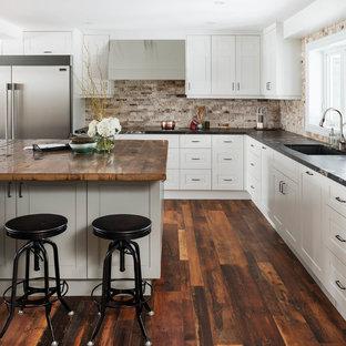 Modelo de cocina en L, clásica renovada, grande, abierta, con puertas de armario blancas, una isla, armarios con paneles empotrados, salpicadero beige, salpicadero de azulejos de piedra, electrodomésticos de acero inoxidable y suelo de madera oscura