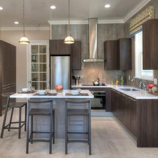 This is an example of a mid-sized modern l-shaped eat-in kitchen in San Diego with an undermount sink, flat-panel cabinets, medium wood cabinets, solid surface benchtops, grey splashback, porcelain splashback, stainless steel appliances, porcelain floors and with island.