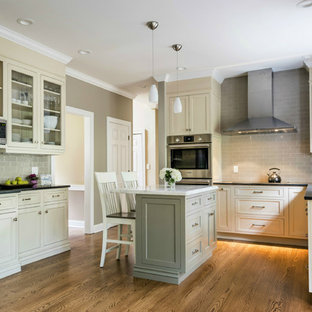 Design ideas for a small transitional u-shaped open plan kitchen in Other with an undermount sink, beaded inset cabinets, beige cabinets, grey splashback, ceramic splashback, stainless steel appliances, medium hardwood floors, with island, limestone benchtops and brown floor.