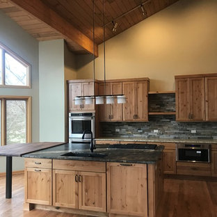 This is an example of a large country l-shaped open plan kitchen in Chicago with an undermount sink, shaker cabinets, medium wood cabinets, granite benchtops, green splashback, slate splashback, stainless steel appliances, medium hardwood floors, with island, brown floor and black benchtop.