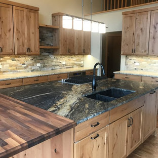 Photo of a large country l-shaped open plan kitchen in Chicago with an undermount sink, shaker cabinets, medium wood cabinets, granite benchtops, green splashback, slate splashback, stainless steel appliances, medium hardwood floors, with island, brown floor and black benchtop.