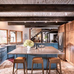На фото: огромная п-образная кухня в стиле рустика с фасадами в стиле шейкер, синими фасадами, столешницей из кварцевого композита, островом, раковиной в стиле кантри, техникой из нержавеющей стали и серой столешницей с