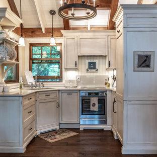 他の地域の小さいラスティックスタイルのおしゃれなコの字型キッチン (ダブルシンク、インセット扉のキャビネット、ヴィンテージ仕上げキャビネット、クオーツストーンカウンター、ベージュキッチンパネル、石スラブのキッチンパネル、パネルと同色の調理設備、濃色無垢フローリング、アイランドなし、茶色い床、ベージュのキッチンカウンター) の写真