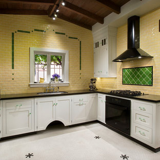 This is an example of a mid-sized traditional u-shaped separate kitchen in Phoenix with a double-bowl sink, beaded inset cabinets, white cabinets, granite benchtops, yellow splashback, ceramic splashback, black appliances, ceramic floors and no island.