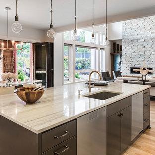 バンクーバーの大きいモダンスタイルのおしゃれなキッチン (ドロップインシンク、フラットパネル扉のキャビネット、ステンレスキャビネット、大理石カウンター、白いキッチンパネル、シルバーの調理設備の、淡色無垢フローリング) の写真
