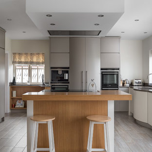 Medium sized contemporary u-shaped kitchen/diner in Other with flat-panel cabinets, grey cabinets, granite worktops, integrated appliances, medium hardwood flooring, an island and grey floors.