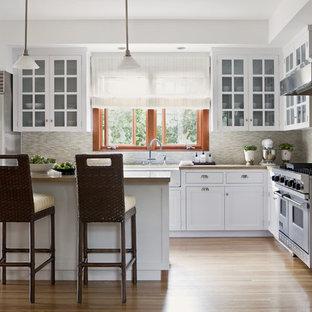 Immagine di una cucina a L chic con elettrodomestici in acciaio inossidabile, lavello stile country, ante di vetro, ante bianche, top in cemento, paraspruzzi beige e paraspruzzi con piastrelle a listelli