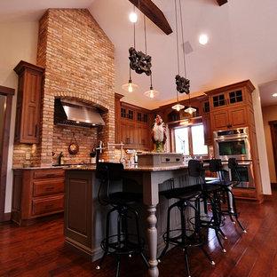 Immagine di una cucina abitabile stile americano con lavello stile country, ante in legno scuro, top in granito, elettrodomestici in acciaio inossidabile e isola