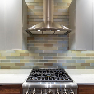 Small transitional enclosed kitchen ideas - Enclosed kitchen - small transitional l-shaped porcelain tile and brown floor enclosed kitchen idea in Other with an undermount sink, shaker cabinets, medium tone wood cabinets, quartz countertops, metallic backsplash, glass tile backsplash, stainless steel appliances, a peninsula and white countertops