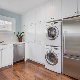 Inredning av ett klassiskt l-kök, med en undermonterad diskho, släta luckor, vita skåp, rostfria vitvaror och mörkt trägolv