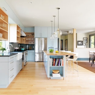 This is an example of a mid-sized contemporary l-shaped open plan kitchen in Burlington with a farmhouse sink, flat-panel cabinets, turquoise cabinets, granite benchtops, green splashback, glass tile splashback, stainless steel appliances, light hardwood floors and with island.