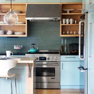 バーリントンの中サイズのコンテンポラリースタイルのおしゃれなキッチン (エプロンフロントシンク、フラットパネル扉のキャビネット、ターコイズのキャビネット、御影石カウンター、緑のキッチンパネル、セラミックタイルのキッチンパネル、シルバーの調理設備の、淡色無垢フローリング) の写真