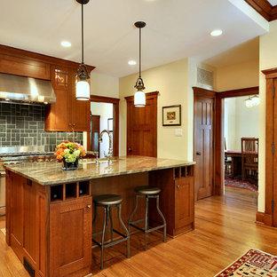 Foto på ett amerikanskt kök, med skåp i shakerstil, skåp i mellenmörkt trä, granitbänkskiva och grått stänkskydd