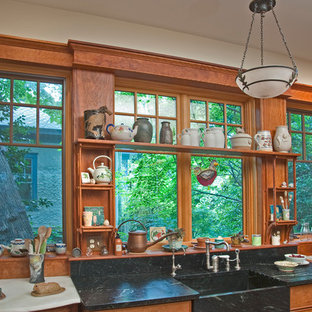 Mid-sized craftsman kitchen ideas - Example of a mid-sized arts and crafts kitchen design in Atlanta with an integrated sink, open cabinets, soapstone countertops, brown backsplash and window backsplash