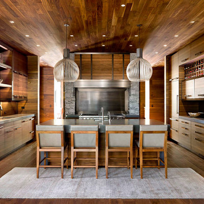 Inspiration for a large rustic u-shaped dark wood floor and brown floor eat-in kitchen remodel in Other with an undermount sink, flat-panel cabinets, dark wood cabinets, metallic backsplash, stainless steel appliances, an island, solid surface countertops and metal backsplash