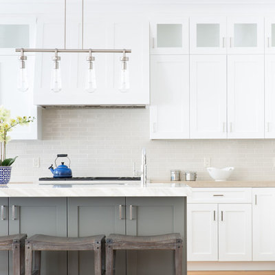 Example of a large transitional medium tone wood floor and beige floor eat-in kitchen design in San Francisco with a farmhouse sink, shaker cabinets, white cabinets, marble countertops, beige backsplash, ceramic backsplash, stainless steel appliances, an island and beige countertops