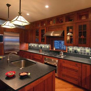 Bild på ett stort amerikanskt u-kök, med skåp i shakerstil, rostfria vitvaror, en undermonterad diskho, skåp i mörkt trä, grönt stänkskydd, en köksö och mellanmörkt trägolv
