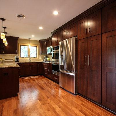 Eat-in kitchen - craftsman u-shaped eat-in kitchen idea in Detroit with an undermount sink, shaker cabinets, medium tone wood cabinets, quartz countertops, beige backsplash, stone tile backsplash and stainless steel appliances