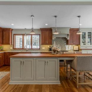 デトロイトの大きいトラディショナルスタイルのおしゃれなキッチン (アンダーカウンターシンク、シェーカースタイル扉のキャビネット、木材カウンター、緑のキッチンパネル、シルバーの調理設備、無垢フローリング、中間色木目調キャビネット、サブウェイタイルのキッチンパネル) の写真