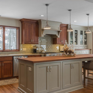 Inspiration for a large traditional l-shaped eat-in kitchen in Detroit with an undermount sink, shaker cabinets, green cabinets, wood benchtops, green splashback, glass tile splashback, stainless steel appliances, medium hardwood floors, with island and brown floor.