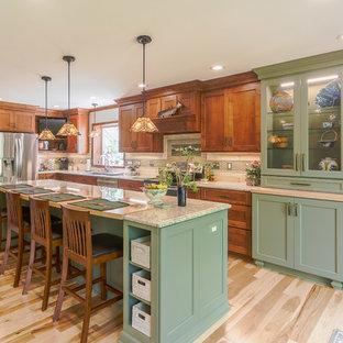 Idéer för ett stort amerikanskt beige l-kök, med en undermonterad diskho, granitbänkskiva, beige stänkskydd, stänkskydd i kalk, rostfria vitvaror, ljust trägolv, en köksö, skåp i shakerstil, skåp i mellenmörkt trä och beiget golv