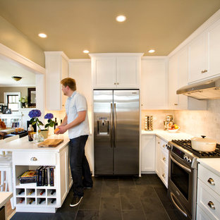 Example of a mid-sized classic u-shaped slate floor enclosed kitchen design in Portland with quartz countertops, stainless steel appliances, white cabinets, a farmhouse sink, recessed-panel cabinets, gray backsplash, a peninsula and marble backsplash