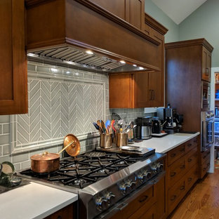 Design ideas for a large arts and crafts l-shaped eat-in kitchen in Chicago with with island, shaker cabinets, medium wood cabinets, granite benchtops, green splashback, porcelain splashback, stainless steel appliances, medium hardwood floors, brown floor, white benchtop and a farmhouse sink.