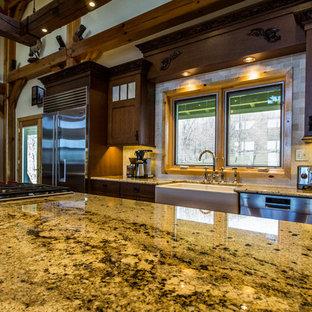 Design ideas for an expansive classic kitchen/diner in Other with a belfast sink, brown cabinets, granite worktops, beige splashback, marble splashback, stainless steel appliances, medium hardwood flooring and multiple islands.
