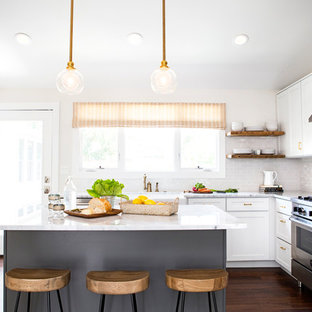 Country kitchen photo in Austin with white backsplash and an island