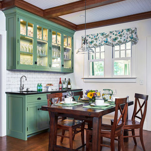 Inspiration for a large traditional single-wall eat-in kitchen in New York with shaker cabinets, green cabinets, granite benchtops, white splashback, ceramic splashback, stainless steel appliances, medium hardwood floors, beige floor, black benchtop and an undermount sink.