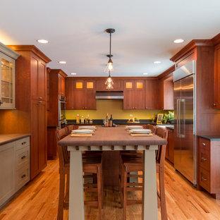 Imagen de cocina comedor en U, de estilo americano, grande, con fregadero sobremueble, armarios con paneles lisos, puertas de armario de madera oscura, encimera de granito, salpicadero amarillo, electrodomésticos de acero inoxidable, suelo de madera clara y una isla