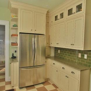 Inredning av ett amerikanskt avskilt, litet u-kök, med en enkel diskho, luckor med profilerade fronter, vita skåp, grönt stänkskydd, rostfria vitvaror, linoleumgolv, stänkskydd i tunnelbanekakel och bänkskiva i återvunnet glas