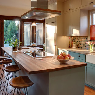 Example of a mid-sized classic galley medium tone wood floor eat-in kitchen design in Los Angeles with a farmhouse sink, quartz countertops, multicolored backsplash, beige cabinets, shaker cabinets, ceramic backsplash, an island and paneled appliances