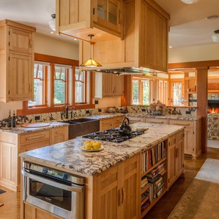 Inspiration for a large traditional u-shaped kitchen/diner in Portland Maine with a belfast sink, recessed-panel cabinets, light wood cabinets, granite worktops, brown splashback, stone slab splashback, stainless steel appliances, light hardwood flooring and an island.