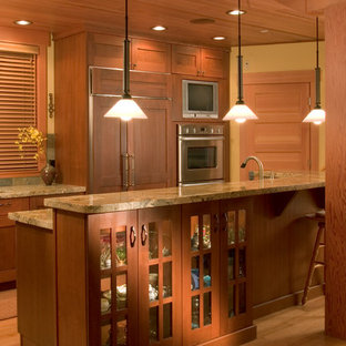 Design ideas for a mid-sized arts and crafts kitchen in Seattle with a drop-in sink, light wood cabinets, granite benchtops, multi-coloured splashback, cement tile splashback, stainless steel appliances, light hardwood floors and with island.