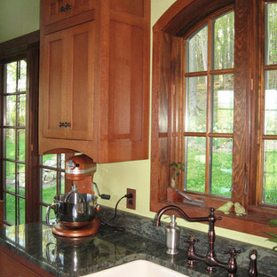 Photo of a mid-sized arts and crafts u-shaped eat-in kitchen in New York with a farmhouse sink, flat-panel cabinets, medium wood cabinets, granite benchtops, brown splashback, stone slab splashback, white appliances, porcelain floors and a peninsula.