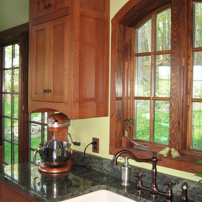 Inspiration for a mid-sized craftsman u-shaped porcelain tile eat-in kitchen remodel in New York with a farmhouse sink, flat-panel cabinets, medium tone wood cabinets, granite countertops, brown backsplash, stone slab backsplash, white appliances and a peninsula