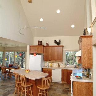 他の地域のおしゃれなアイランドキッチン (シングルシンク、レイズドパネル扉のキャビネット、中間色木目調キャビネット、タイルカウンター、白い調理設備、スレートの床) の写真