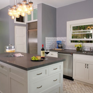 Inspiration for a mid-sized arts and crafts l-shaped kitchen in Los Angeles with an undermount sink, shaker cabinets, white cabinets, soapstone benchtops, white splashback, subway tile splashback, stainless steel appliances, marble floors and with island.