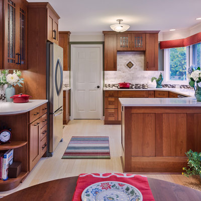 Large arts and crafts u-shaped bamboo floor eat-in kitchen photo in Detroit with an undermount sink, shaker cabinets, medium tone wood cabinets, quartzite countertops, beige backsplash, stone tile backsplash, stainless steel appliances and a peninsula