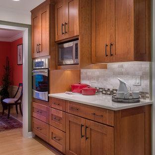 デトロイトの広いおしゃれなキッチン (シェーカースタイル扉のキャビネット、中間色木目調キャビネット、珪岩カウンター、ベージュキッチンパネル、石タイルのキッチンパネル、シルバーの調理設備、竹フローリング) の写真