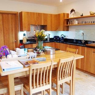 コーンウォールの大きいエクレクティックスタイルのおしゃれなキッチン (一体型シンク、フラットパネル扉のキャビネット、中間色木目調キャビネット、御影石カウンター、メタリックのキッチンパネル、シルバーの調理設備の、ライムストーンの床、ベージュの床、黒いキッチンカウンター) の写真