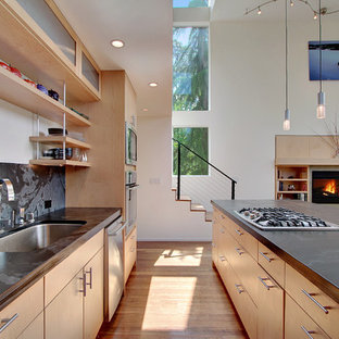 Inspiration for a modern open plan kitchen in Seattle with a single-bowl sink, open cabinets, light wood cabinets, black splashback, stone slab splashback and stainless steel appliances.
