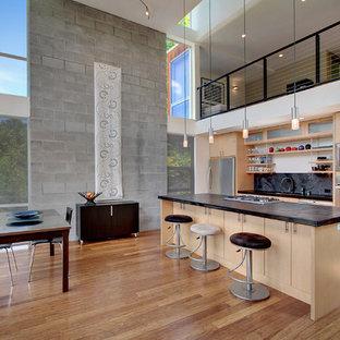 Modelo de cocina comedor de galera, minimalista, con salpicadero negro, salpicadero de losas de piedra, armarios con paneles lisos, puertas de armario de madera clara y electrodomésticos de acero inoxidable
